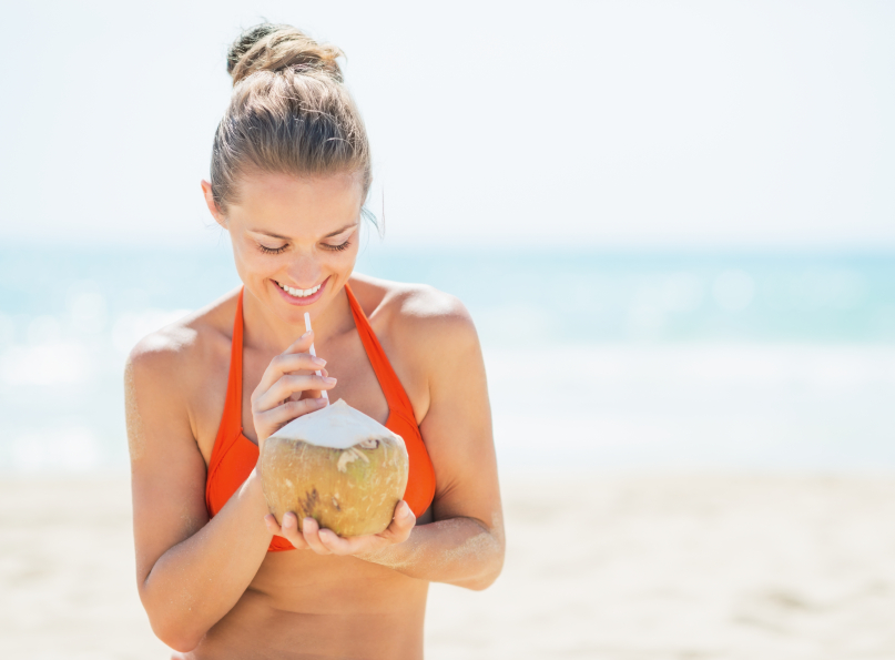 Happy young woman drinking coconut milk on beach